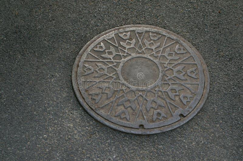 Metallcirkel av avrinningvatten på trottoar royaltyfria foton