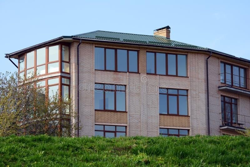 Metalldeckung Großes modernes Haus mit großen Fenstern und Balkonen Regnen Sie Gosse auf die Dachoberseite des Hauses Metalldach  stockbild