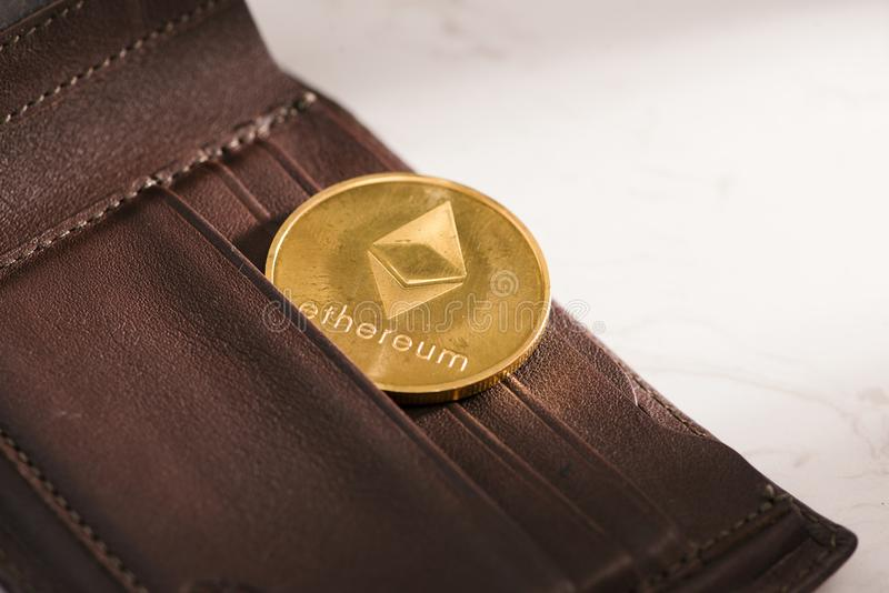 Metallethereum i brun läderplånbok Bitcoin - modernt faktiskt royaltyfri foto