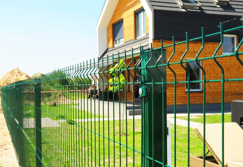 Metallfäktning med det utomhus- moderna huset Metallstaketdesign arkivbild
