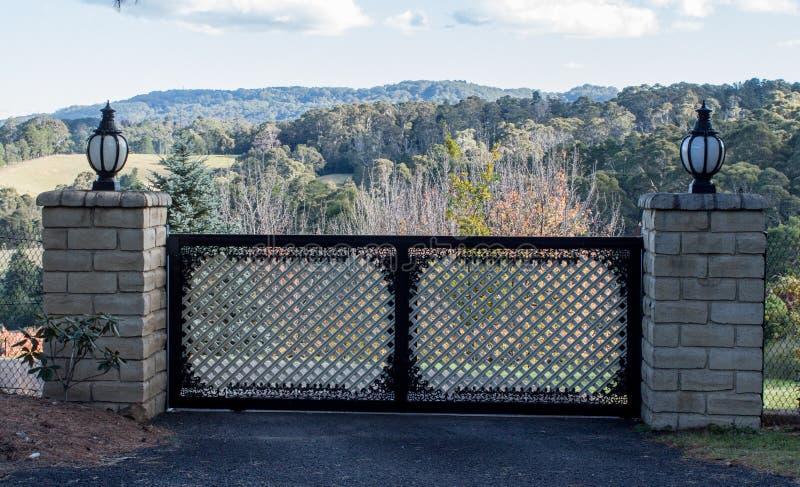Metallfahrstraßen-Eingangstore stellten in Ziegelsteinzaun mit Gartenbäumen und in ländlichen Abhang im Hintergrund ein stockfotografie