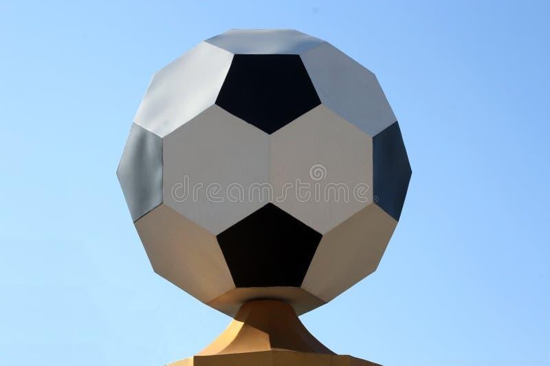 Metallfotbollboll på en sockel på en solig dag mot himmelslutet upp fotografering för bildbyråer
