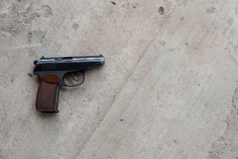 Metallgewehr auf einem grauen konkreten Hintergrund Draufsicht, flache Lage, Kopienraum stockfoto