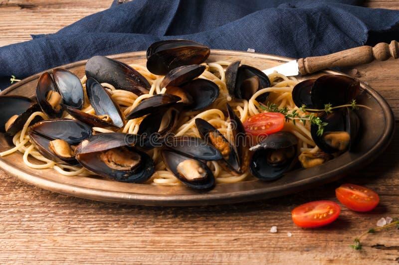 Metallgoldene Platte mit k?stlichen traditionellen italienischen Spaghettis und den Miesmuscheln gekocht in der So?e mit Tomaten lizenzfreie stockfotos