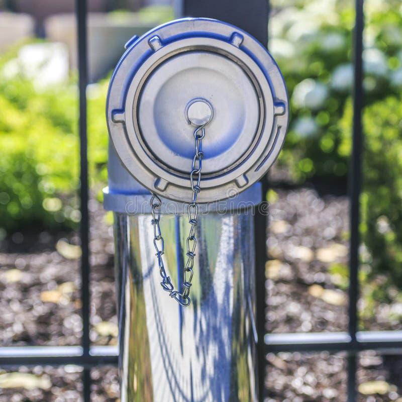 Metallhydrant gegen einen Zaun an einem sonnigen Tag lizenzfreie stockbilder