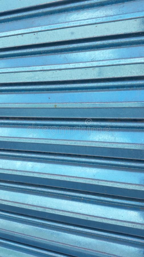 Metallic blue aluminum courtain. Closeup of a closed Metallic blue aluminum curtain with reflection of daylight royalty free stock photos