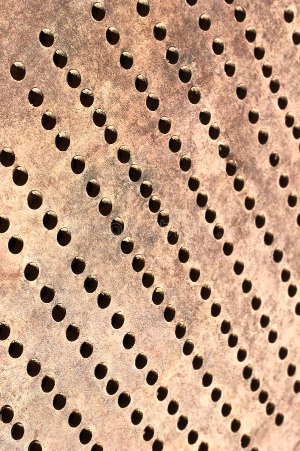 Metallic bronze textured background with pattern of round cells in diagonal, vertical. Metallic bronze textured background with pattern of round cells diagonally royalty free stock photos