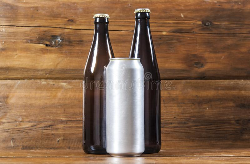 Metallic can and glass bottle of beer on a wooden background. Blank metallic can and glass bottle of beer on a wooden background stock image