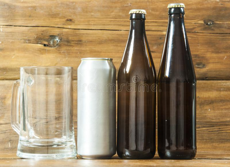 Metallic can and glass bottle of beer on a wooden background. Blank metallic can and glass bottle of beer on a wooden background stock photography