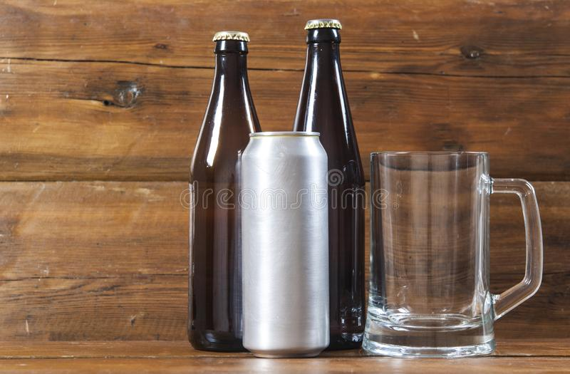 Metallic can and glass bottle of beer on a wooden background. Blank metallic can and glass bottle of beer on a wooden background royalty free stock images