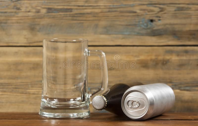 Metallic can and glass bottle of beer on a wooden background. Blank metallic can and glass bottle of beer on a wooden background royalty free stock photo