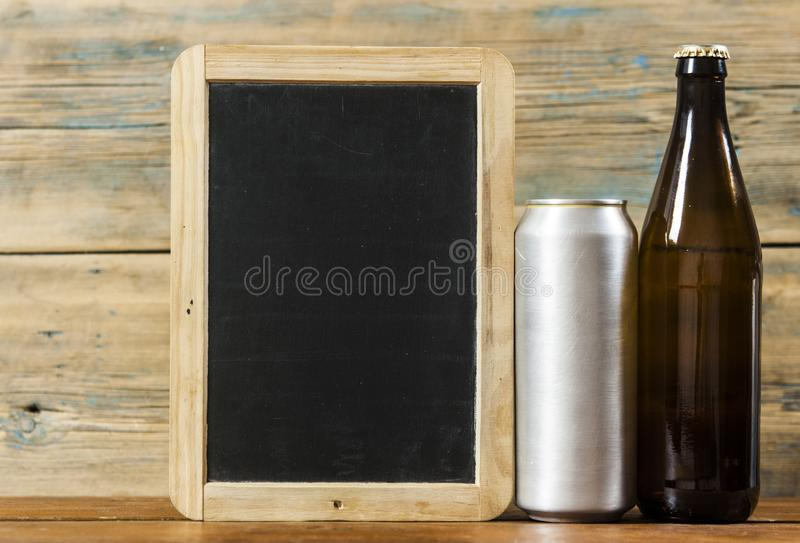 Metallic can and glass bottle of beer on a wooden background. Blank metallic can and glass bottle of beer on a wooden background stock images
