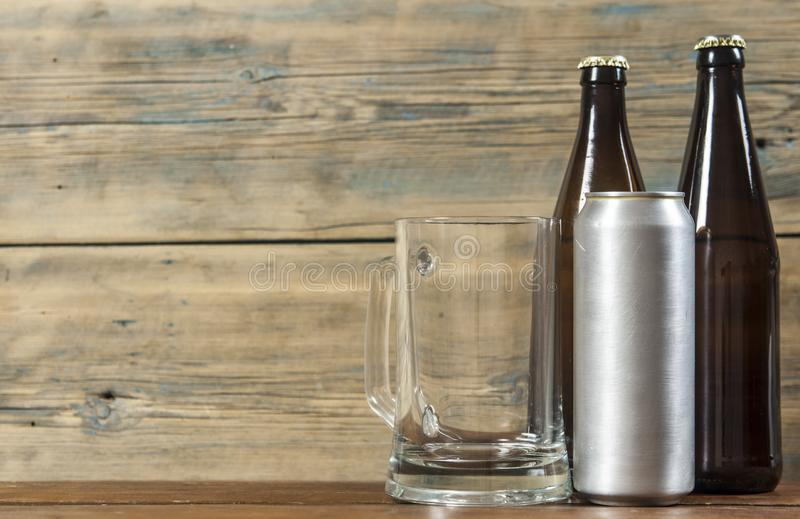 Metallic can and glass bottle of beer on a wooden background. Blank metallic can and glass bottle of beer on a wooden background royalty free stock photography