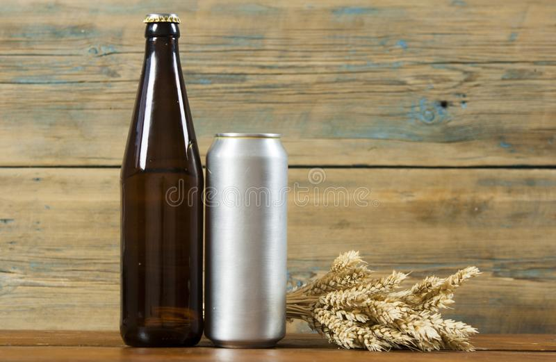 Metallic can and glass bottle of beer on a wooden background. Blank metallic can and glass bottle of beer on a wooden background royalty free stock image