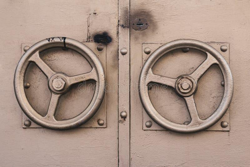 The metallic door knob in the shape of gilded steering wheel. Old door golden color with two door round handles royalty free stock image
