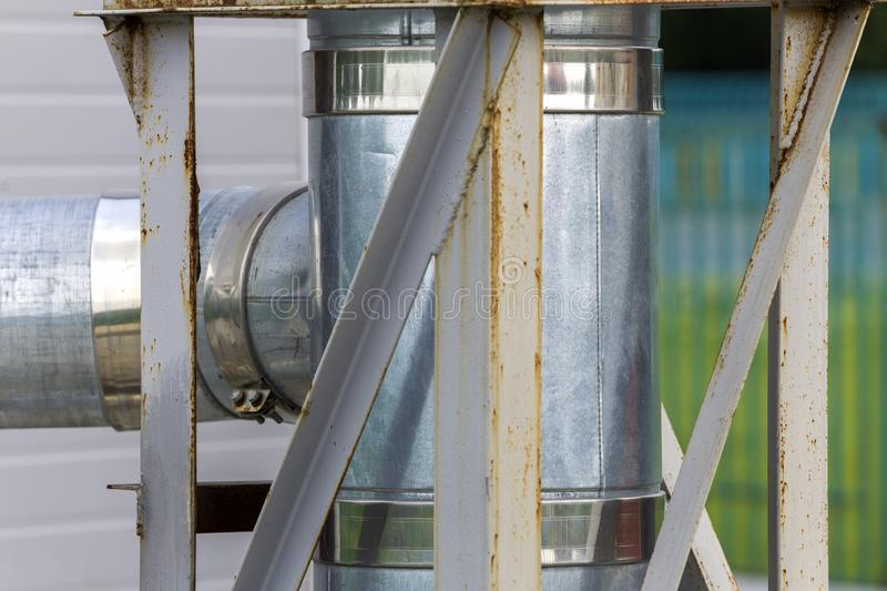 Metallic exhaust smoke pipes installed on house exterior wall stock images