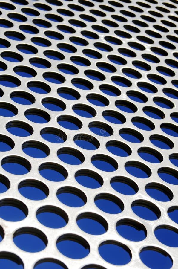 Metallic Grid. Aluminum perforated grid against a blue sky under sun light royalty free stock photos
