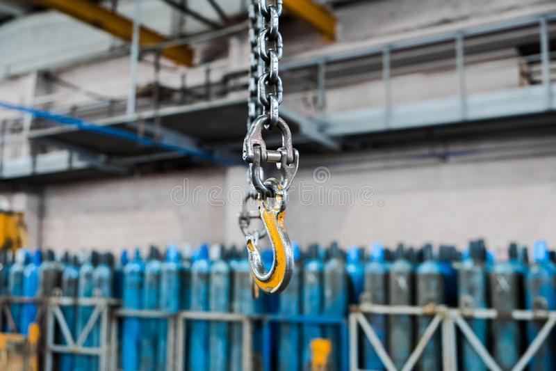 Metallic industrial hook for lifting heavy thing in the factory. Crane hooks on a thick chain inside the factory floor. Metallic industrial hook for lifting royalty free stock images