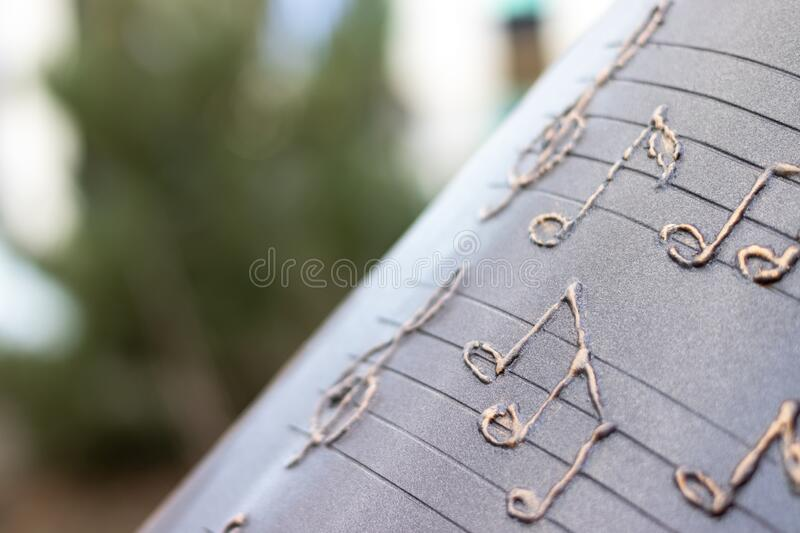 Metallic musical notes and a treble clef on a stave on a notebook against a blurred green background. Selective focus. Closeup view royalty free stock photography