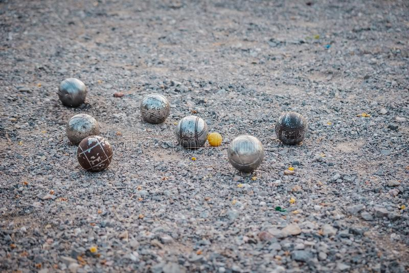 Metallic petanque balls and a small yellow jack. royalty free stock photo