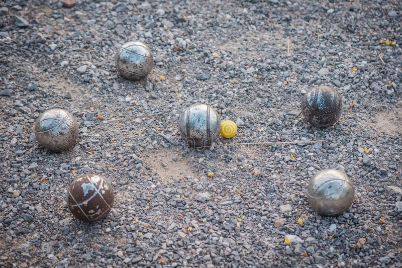Metallic petanque balls and a small yellow jack. royalty free stock images