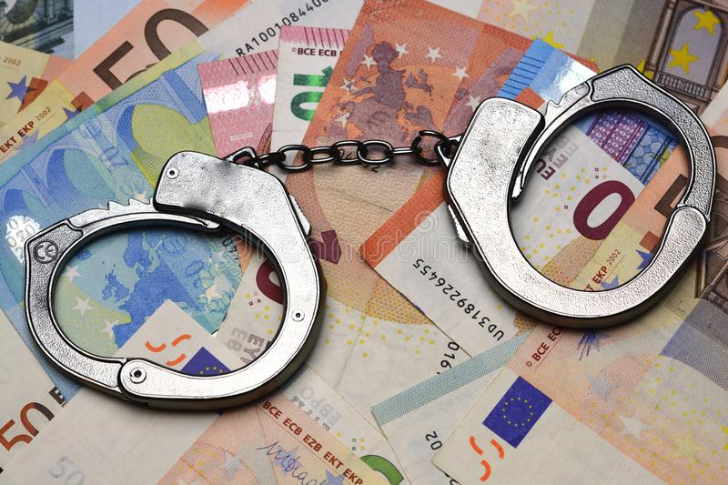 Metallic police handcuffs on euro banknotes suggesting corruption or criminal delinquency. Metallic police handcuffs on euro bills suggesting corruption or royalty free stock image