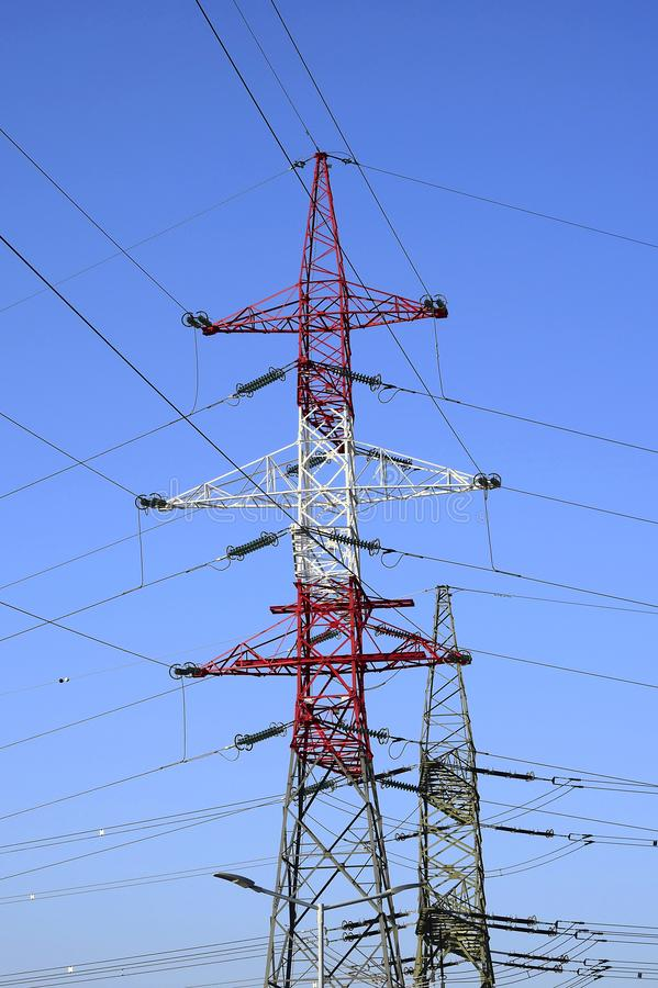 Metallic pylons of high-voltage power lines against a blue sky stock images