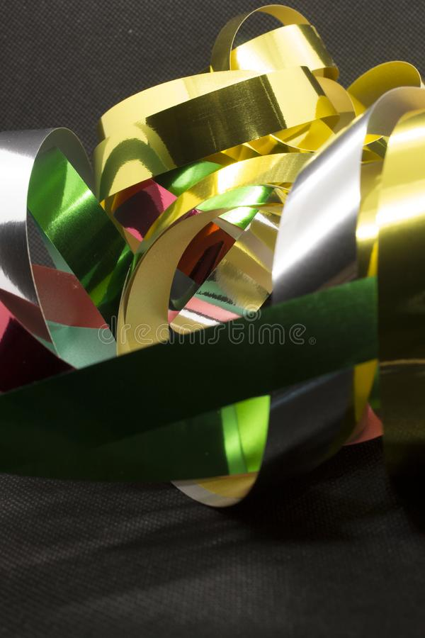 Metallic Ribbons. This is a photograph of Gold,Silver,Green and Red Metallic Ribbons placed infront of a Black background stock photos