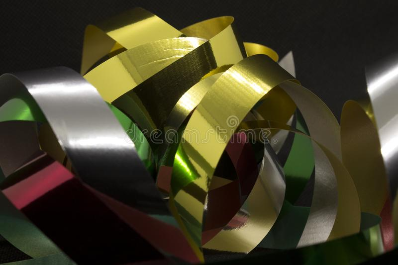 Metallic Ribbons. This is a photograph of Gold,Silver,Green and Red Metallic Ribbons placed infront of a Black background stock image