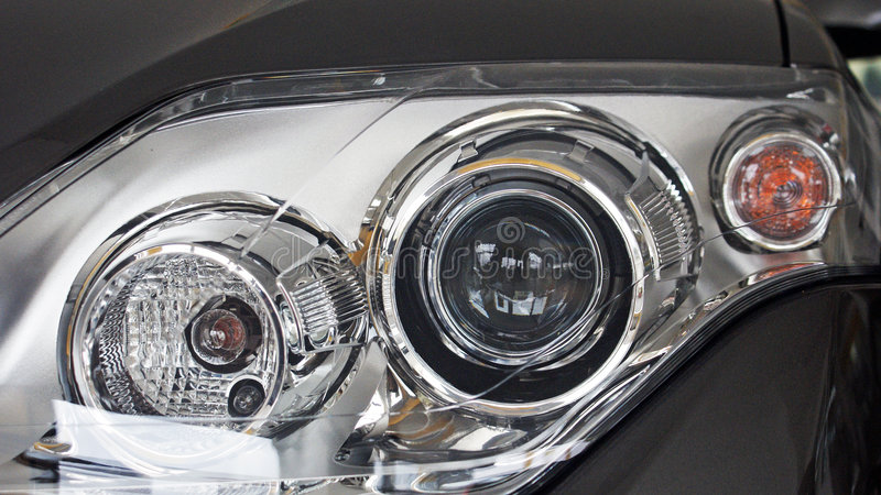 Metallic silver car headlight detail close up royalty free stock image