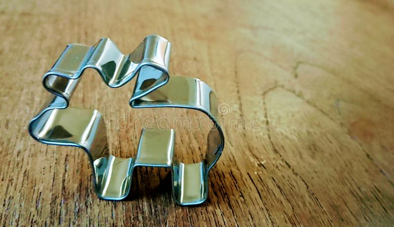 Metallic silver shape for biscuits and cookies in the form of a reindeer is standing on a wooden table stock photos