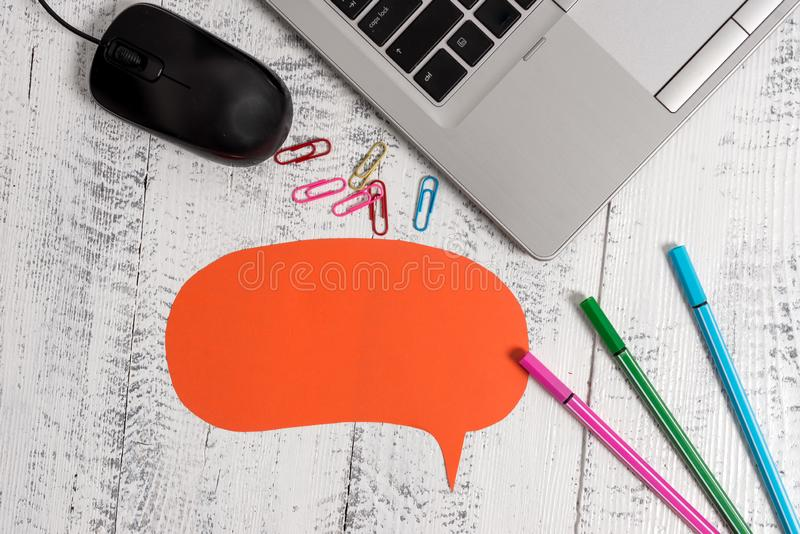 Trendy metallic laptop speech bubble colored clips pens mouse lying wooden rustic vintage table. Personal computer stock image