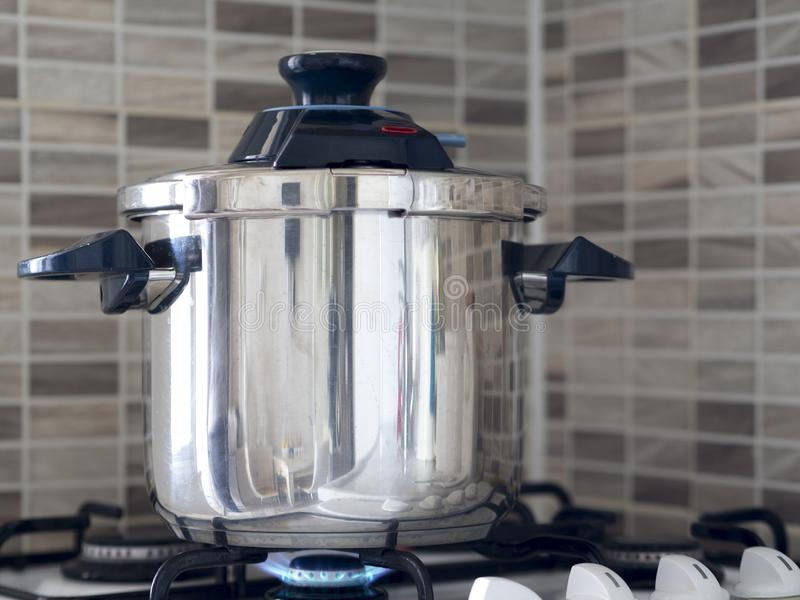 Metallic steel pressure cooker standing on the oven in the kitchen and cooking being cooked royalty free stock photography