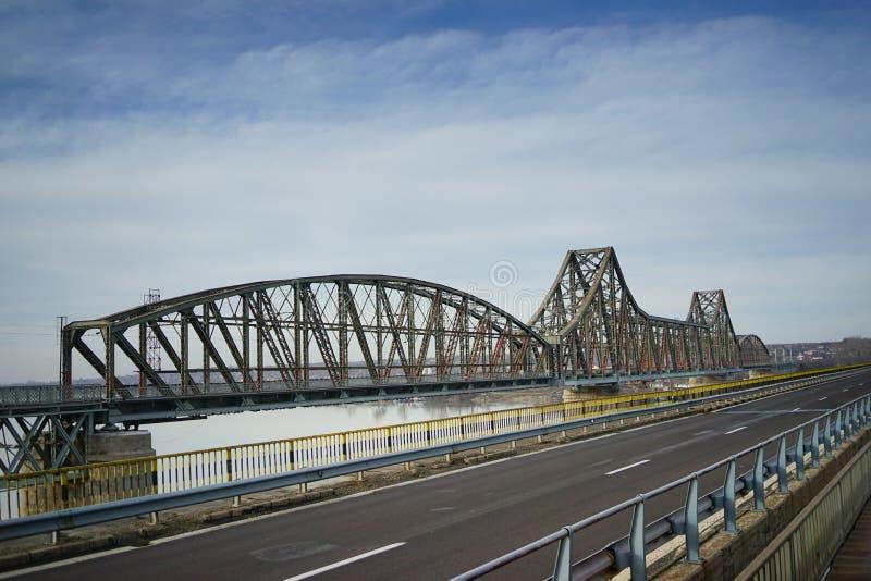 Farraday cage. Metallic train bridge over Danube. FeteÈ™ti Romania. Blue sky, tarmac road and metallic train bridge stock photos