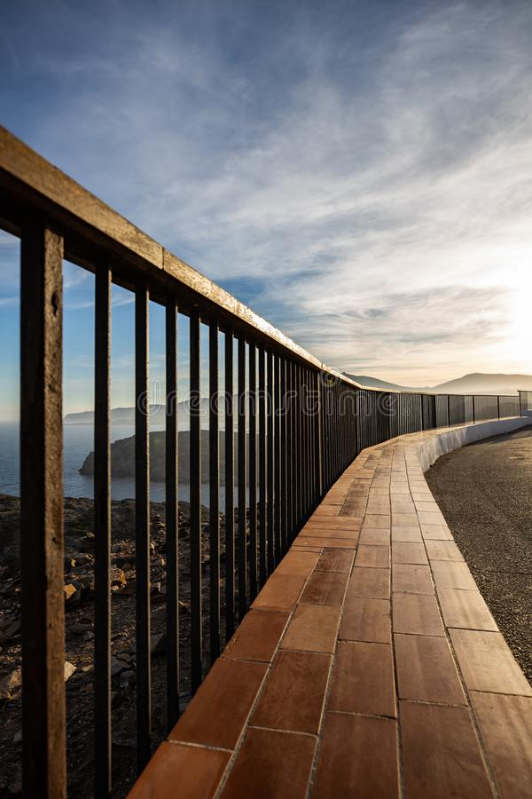 Metallic and wooden railing on a coast cliff illuminated by the sunset light royalty free stock images