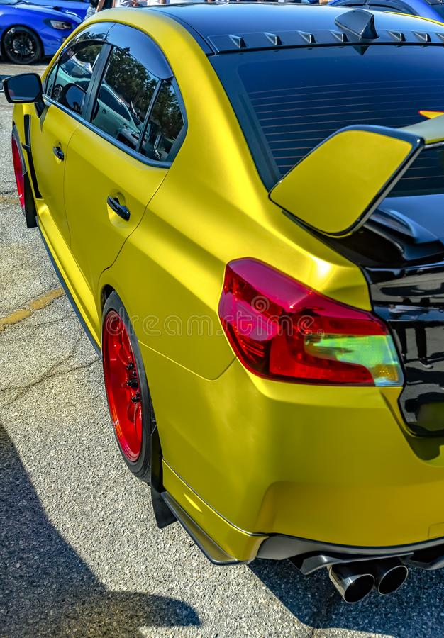 Metallic yellow car with large spoiler and red rims royalty free stock photos