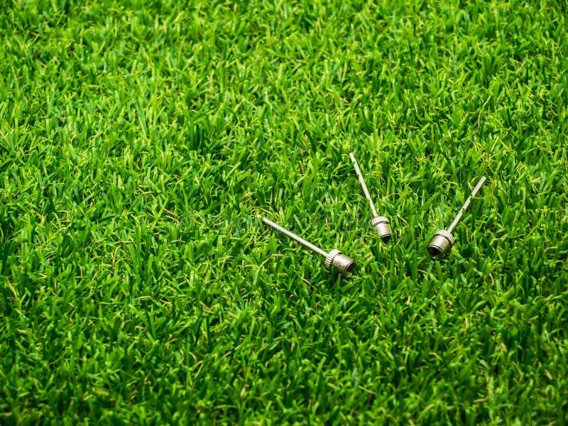 Metallinflationsnadel auf dem Gras lizenzfreies stockbild