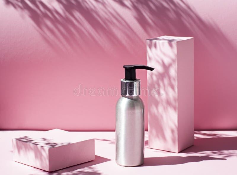 Metallische kosmetische Flasche auf dem rosa Hintergrund mit grellem Licht lizenzfreie stockfotos
