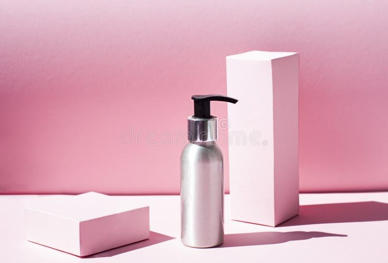 Metallische kosmetische Flasche auf dem rosa Hintergrund mit grellem Licht stockfotos