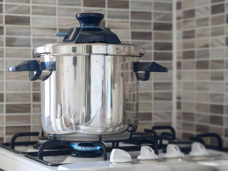 Metallische Stahldampfkochtopfstellung auf dem Ofen in der Küche und im Kochen gekocht werden stockfotografie