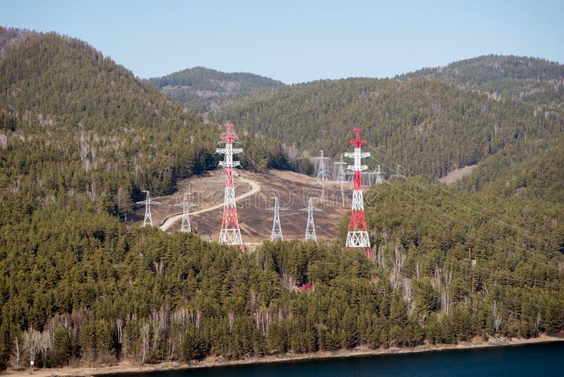 Metallische Unterstützungen von obenliegenden Stromleitungen für Strom unter dem sibirischen Wald, auf der Flussbank lizenzfreies stockfoto