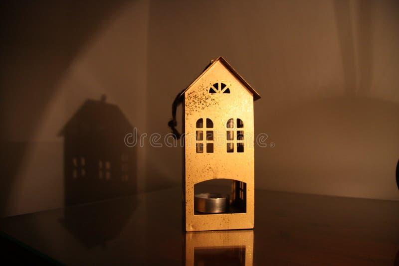 Metallischer Kerzenständer in Form eines Hauses auf dem Tisch am dunklen Abend mit Lampenlicht stockbilder