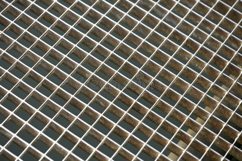 Metallisches Fenster des Gefängnisses mit diagonalen Straßenlinien Makrohintergrundschöne kunst der kleinen Quadranten in Druckpr stockfotografie
