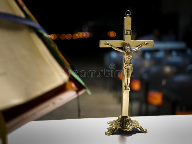 Metallisches Kreuz gesetzt auf einen Altar vor einer katholischen Masse nachts mit unscharfem Hintergrund stockfotografie