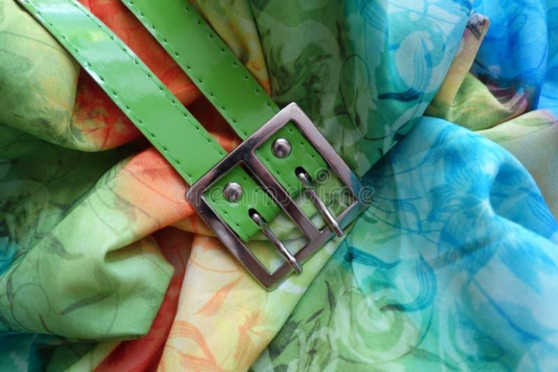 Metallisk buckla och grönt bälte på rayon royaltyfri bild