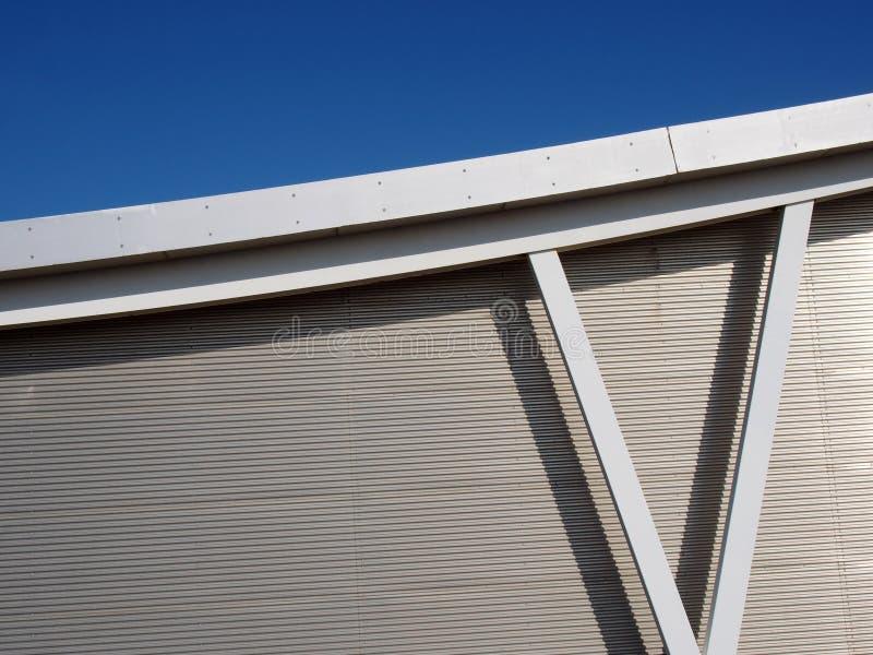 Metallisk cladding på modern industribyggnad med stålbalkar och krökt takstråle mot en blå himmel arkivbilder