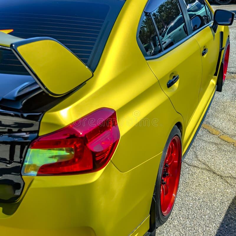 Metallisk gul bil med den ljusa röda hjulkanten arkivbild