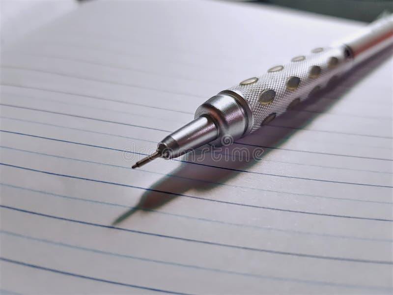 Metallisk mekanisk blyertspenna på foliopapper fotografering för bildbyråer