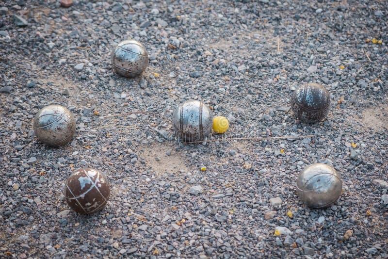 Metalliska petanquebollar och en liten gul st?lar royaltyfria bilder
