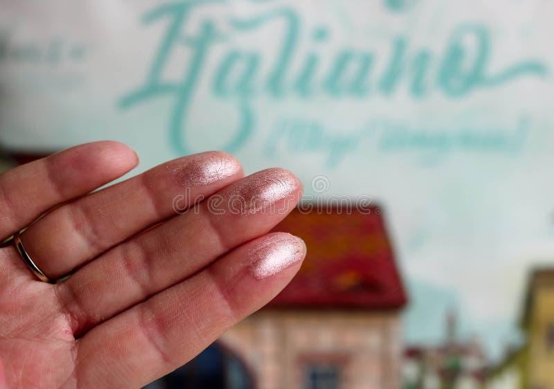 Metalliska provkartor för ögonskuggor på kvinnliga fingrar med färgrik suddig bakgrund royaltyfri foto